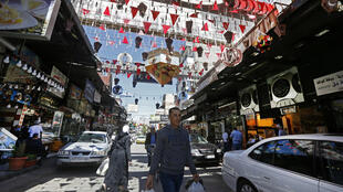 Syrians shop at the Maidan market in the capital Damascus, on April 26, 2020