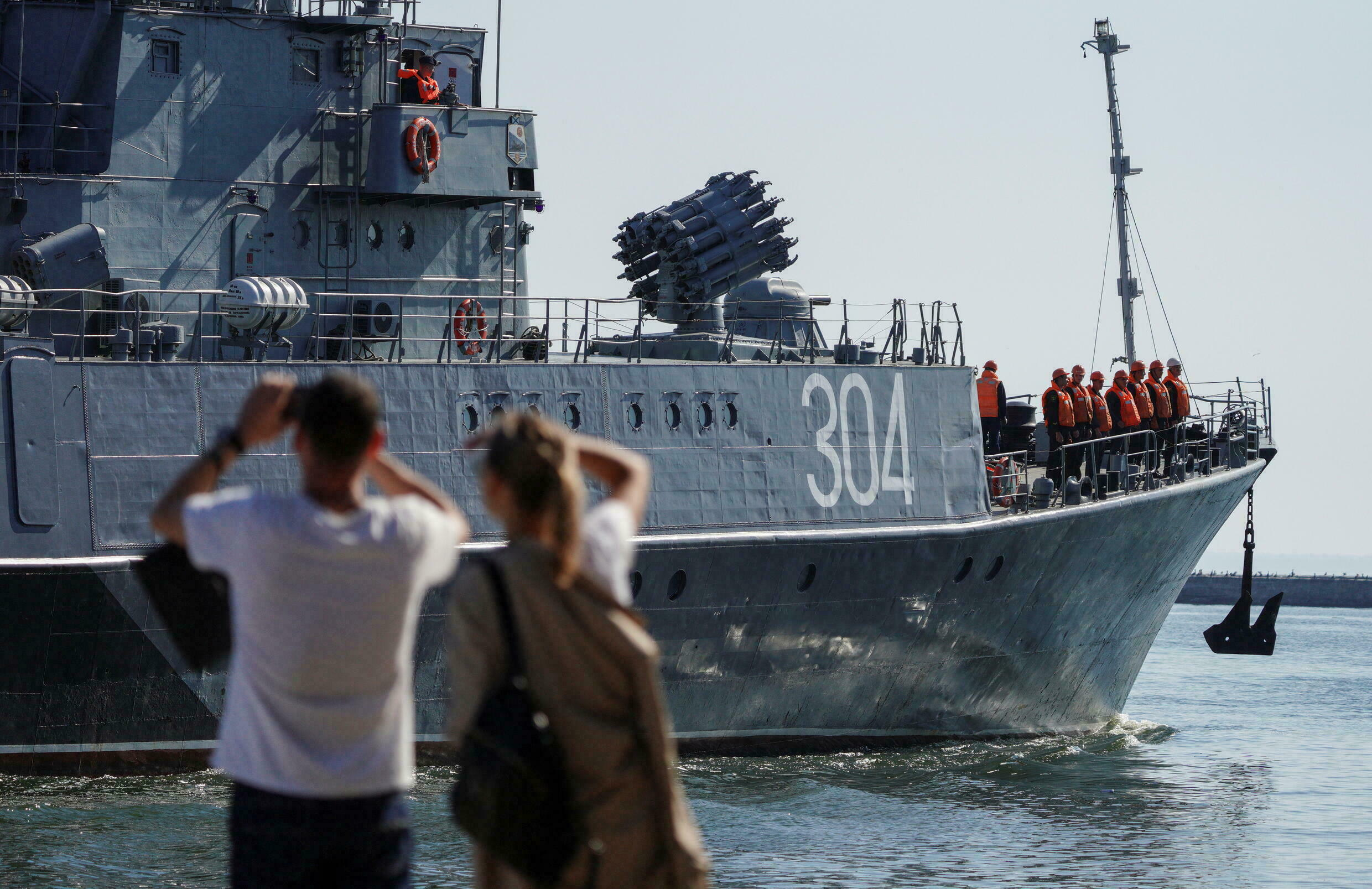 People watch small anti-submarine ship Urengoy leaving a port during naval drills, which are staged by the Baltic Fleet forces of the Russian Navy, in the Baltic Sea town of Baltiysk in Kaliningrad Region, Russia on September 9, 2021.