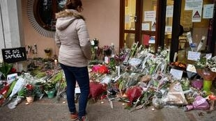 A woman looks at flowers at the entrance of a middle school in Conflans-Sainte-Honorine, 30km northwest of Paris, on October 17, 2020, after a teacher was decapitated by an attacker who was then shot dead by policemen.