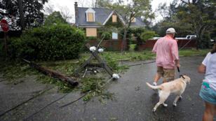 Residentes caminan frente a un poste de electricidad afectado por los fuertes generados por Florence en Wilmington, Carolina del Norte, EE. UU., el 14 de septiembre de 2018.