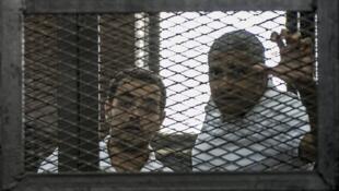 صحافيا الجزيرة الكندي محمد فهمي والمصري باهر محمد أثناء جلسة محاكمة في حزيران/يونيو 2014