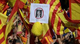Un manifestant tient une pancarte représentant la tête barrée de Carles Puigdemont, récemment évincé de la présidence régionale, à Barcelone le 29octobre.