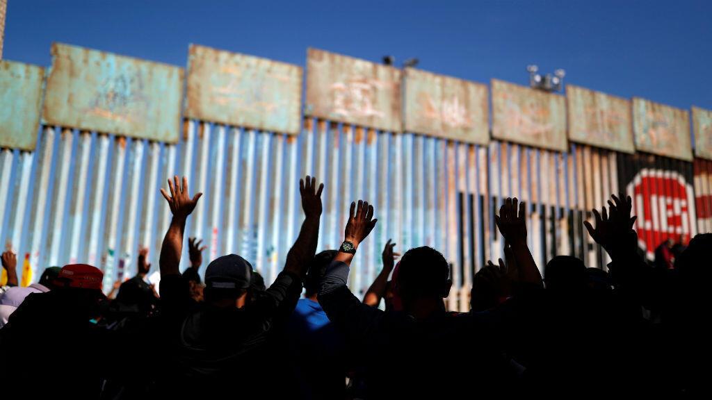 Los migrantes, que forman parte de una caravana de miles que intentan llegar a los Estados Unidos, rezan en la frontera entre México y los Estados Unidos, en Tijuana, México, EL 15 de noviembre de 2018.