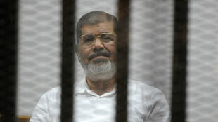 Stringer, AFP file picture | Egypt's deposed president Morsi sits behind the defendants cage during a court trial in Cairo on November 5, 2014