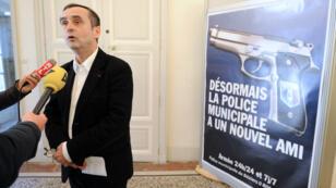 Robert Ménard, 61, poses next to the controversial poster
