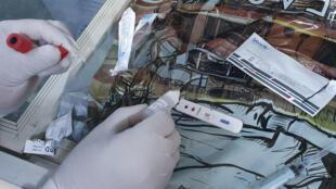 طبيبة ليبية تجري اختبار كوفيد-19 لعينة رفعت من صاحب محل في ضاحية تاجوراء بالعاصمة الليبية طرابلس في 1 حزيران/يونيو 2020