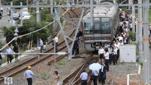 Les passagers d'un train marchent le long des voies ferrées après un séisme, à Osaka, lundi 18 juin 2018.