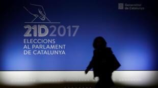 Una mujer pasa frente a un cartel en el principal centro de prensa para las elecciones regionales de mañana en Barcelona, España, el 20 de diciembre de 2017.