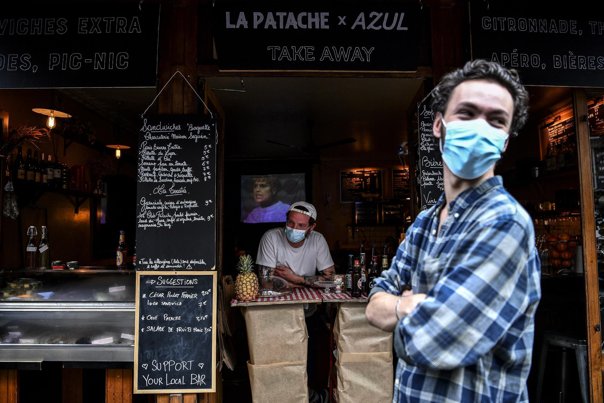 A bartender (C) selling take-away drinks and food and wearing a face mask waits for customers behind a makeshift counter lining the sidewalk in Paris on May 9, 2020