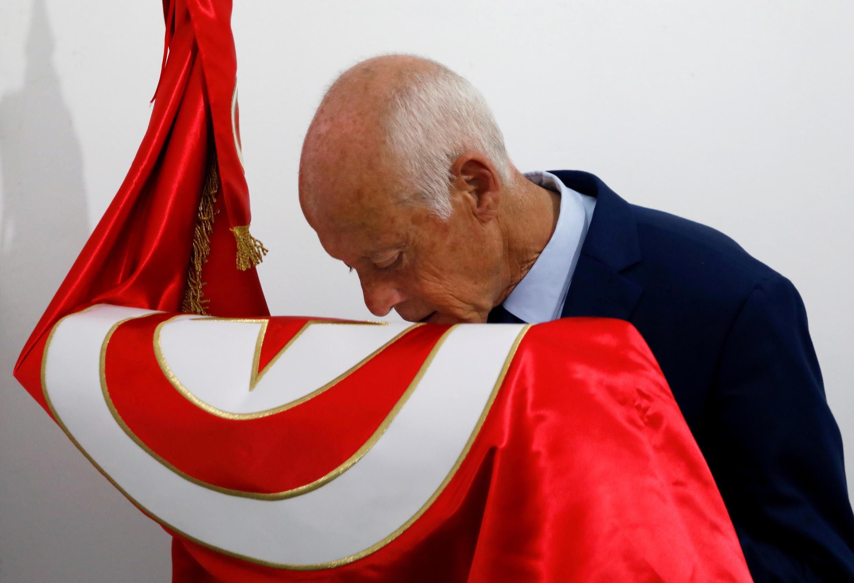 El candidato presidencial Kaïs Saïed besa una bandera tunecina tras los resultados no oficiales de las elecciones presidenciales de Túnez, Túnez, el 15 de septiembre de 2019.