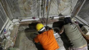Une équipe de restaurateurs grecs replace la plaque de marbre qui recouvre ce que les chrétiens désignent comme étant la tombe de Jésus à Jérusalem.