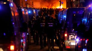 Oficiales de policía avanzan hacia sus colegas mientras se enfrentan con manifestantes catalanes durante la Huelga General de Cataluña.Barcelona, España, 18 de octubre de 2019.