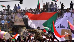 La multitud carga a un militar mientras los manifestantes corean consignas luego de que el ministro de Defensa de Sudán dijo que el presidente Omar al-Bashir había sido detenido.