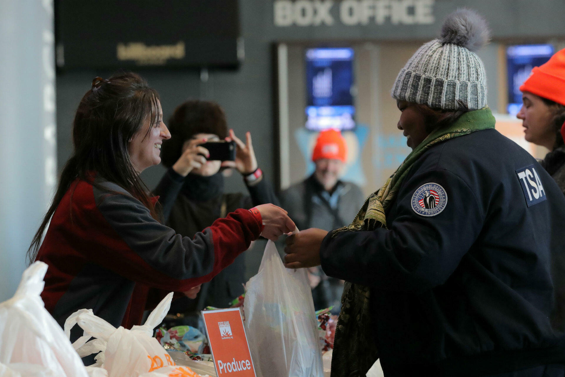 A Transportation Security Administration (TSA) employee receives a donation at a food distribution centre for federal workers impacted by the shutdown, at the Barclays Center in Brooklyn, on January 22, 2019. More than 50,000 TSA officers are working without pay. The agency said on Monday that unscheduled absences among US airport security officers rose to a record 10 percent on Sunday.