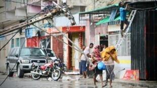 Des gens passent dans une rue de Beira, au Mozambique, le 17 mars 2019 qui a été touchéee par le cyclone Idai