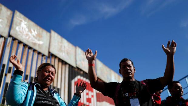 Los migrantes de la primera caravana de miles de centroamericanos que intentan llegar a los Estados Unidos, rezan en la frontera en Tijuana, México, el 15 de noviembre de 2018.