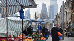 Ciudadanos compran en un mercado, con rascacielos de la City de Londres, el distrito financiero de la ciudad, en el fondo. Londres, Reino Unido, el 15 de enero de 2021.