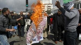 Palestinians burn images of Israeli Prime Minister Benjamin Netanyahu and US President Donald Trump in protest at Israel's decision to withhold Palestinian tax receipts that has helped trigger a suffocating financial crisis