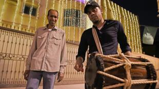 Yasser al-Samak (à droite) arpente les rues de Bilad al-Qadeem, à Bahreïn, pour réveiller les personnes jeûnant pendant le ramadan, le 10 mai 2020