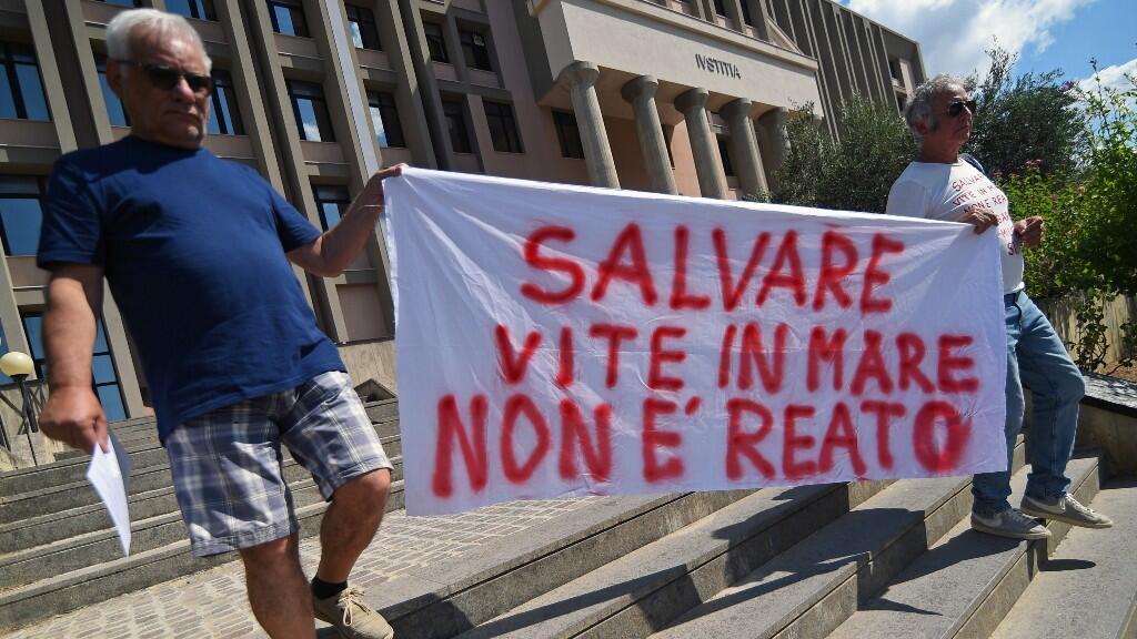 """Unos manifestantes apoyan a Carola Rackete a la salida de los juzgados con una pancarta que reza """"salvar vidas en el mar no es un crimen""""."""