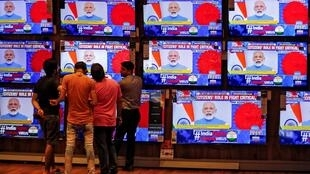 People watch Indian Prime Minister Narendra Modi addressing the nation amid concerns about the spread of coronavirus on TV screens inside a showroom in Ahmedabad, India, March 19, 2020.