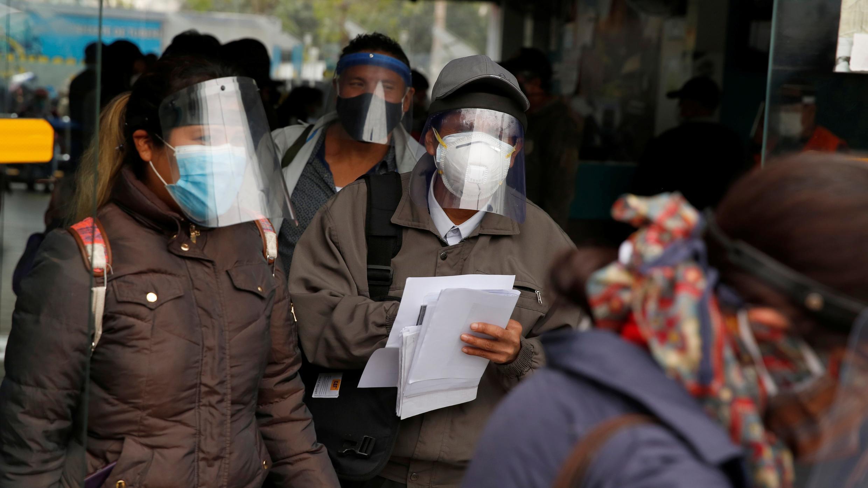 Pasajeros con mascarillas y protectores faciales hacen fila antes de abordar los autobuses, durante el brote de coronavirus, en Lima, Perú, el 15 de julio de 2020.