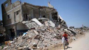 Un enfant passe devant un bâtiment détruit lors du conflit qui opposa l'armée israélienne aux groupes armés palestiniens à Gaza, à l'été 2014.