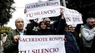 """Miembros de la organización """"Laicos de Osorno"""" con pancartas durante una protesta después de una misa celebrada por enviados especiales del Vaticano en la Catedral de San Mateo en Osorno, Chile, el 17 de junio de 2018."""