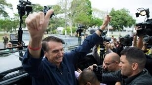 Far-right candidate Jair Bolsonaro waves to supporters after voting in the first round of Brazil's presidential election in Rio de Janeiro on October 7, 2018