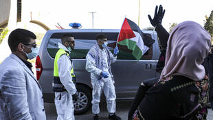 Naji waves the Palestinian flag before being hurried to a nearby hotel for two weeks of isolation alongside other detainees released from Israeli jails
