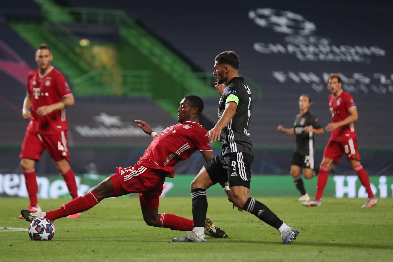 El defensa lateral del Bayern de Múnich David Alaba (l) en un duelo con el centrocampista del Lyon Houssem Aouar, en la semifinal de la Champions, el 19 de agosto de 2020 en Lisboa.