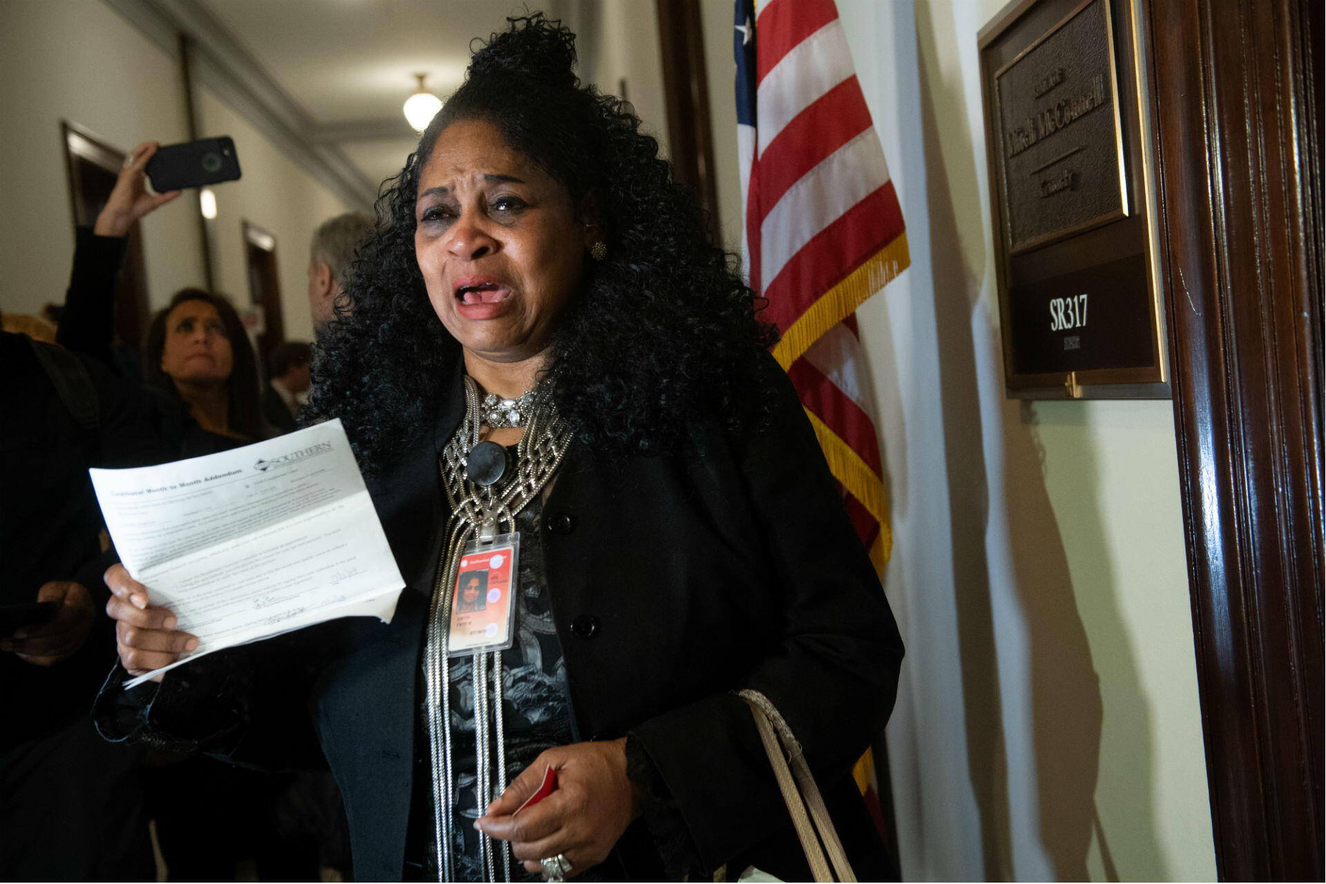 Faye Smith, a furloughed Smithsonian contract worker not paid during the shutdown, holds an unpaid electric bill to present to Senate Majority Leader Mitch McConnell's office on Capitol Hill on January 16, 2019. More than a million contractors have been affected by the shutdown – and, in contrast to federal employees, they are unlikely to receive backpay when business as usual finally resumes.