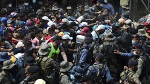 مهاجرون هندوراسيون يقتحمون سياجا للشرطة لدخول غواتيمالا، سعيا لوصول إلى الولايات المتحدة، في 1 تشرين الأول/أكتوبر 2020