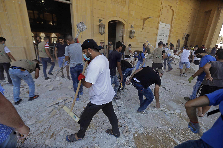 Des gens ramassent les débris dans la mosquée Mohammed al-Amine située dans le centre de Beyrouth, le 5 août 2020.