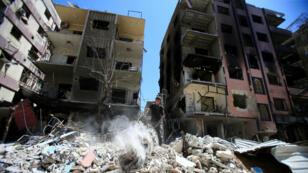 Un garçon se tient debout sur les décombres de bâtiments endommagés dans la ville de Douma en Syrie, le 16 avril 2018.