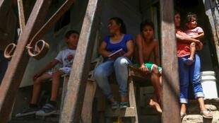 Glenda Lagos sits at the entrance to her tiny home in a poor neighborhood of the Honduran capital Tegucigalpa with four of her six children