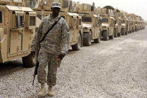 A US soldier stands in front of a line of armoured vehicles at Camp Victory, a giant sprawling military base on the edge of Baghdad airport, in June 2010.