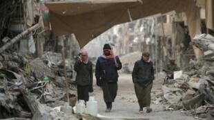 سوريون يسيرون وسط الدمار في مدينة الرقة في 11 كانون الثاني/يناير