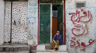 Una mujer palestina se sienta frente a su casa en el campo de refugiados de Jabalia, una de las áreas más densamente pobladas del mundo, en medio de la preocupación por la propagación de la enfermedad por el nuevo coronavirus, en el norte de la Franja de Gaza, el 5 de mayo de 2020.