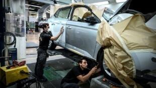 Des réparateurs automobiles d'Aramis Auto travaillent sur une voiture dans un atelier, le 9 juilet 2019 à Donzère