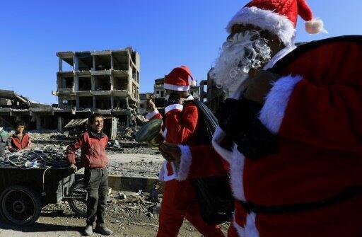 شابان ارتديا زي سانتا كلوز (بابا نويل) يمران أمام طفلين في مدينة الرقة السورية في 26 كانون الأول/ديسمبر 2017