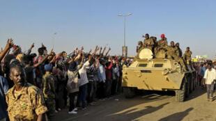 متظاهرون سودانيون يلوحون بعلامة النصر لدى مرور مركبة عسكرية أمام المقر العام للقوات المسلحة في الخرطوم في 7 أبريل/نيسان 2019