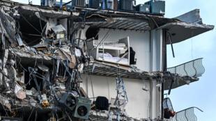 Escombros cuelgan de un edificio que se derrumbó parcialmente en Surfside, al norte de Miami Beach, el 24 de junio de 2021
