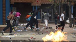 Des personnes venant de piller un magasin CVS Pharmacy de Baltimore prennent la fuite, lundi 27 avril 2015.