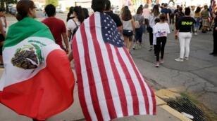 سكان بمدينة إل باسو بولاية تكساس الأمريكية يحملون علمي الولايات المتحدة والمكسيك. 5 أغسطس/آب 2019