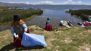 Mujeres indígenas aimaras, limpian la orilla del lago Titicaca en Puerto Perez, departamento de La Paz, Bolivia el 18 de abril de 2018.
