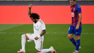 Marcelo, genou à terre et poing levé, rend hommage à George Floyd, un Afro-Américain tué par un policier à Minneapolis, après son but avec le Real contre Eibar, le 14 juin 2020 à Madrid