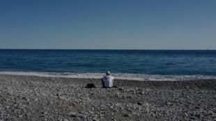 مهاجر يجلس عند شاطئ في مدينة فنتيميليا، 5 آب/اغسطس 2020