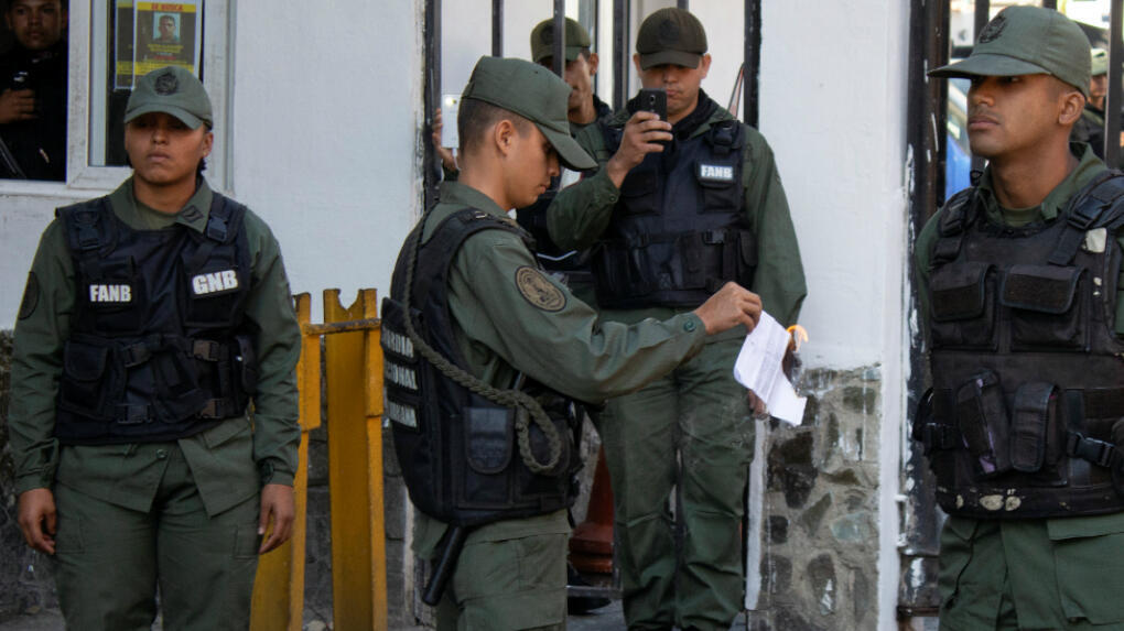 Un integrante de la  Guardia Nacional venezolana quema una copia de la ley de amnistía aprobada por la Asamblea Nacional.