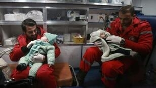 مسعفان سوريان يعتنيان بطفلين داخل سيارة إسعاف ضمن الدفعة الثانية من المرضى الذين يتم إجلاؤهم من الغوطة الشرقية المحاصرة قرب دمشق